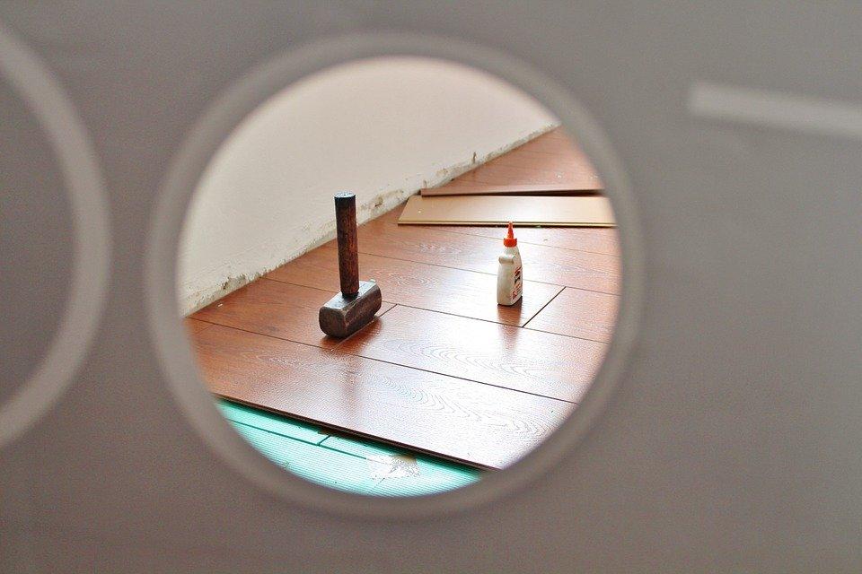 hamer en lijm op onafgewerkte houten vloer